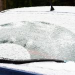 Car windows and wipers covered with snow in winter