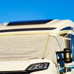 Camper with external thermal screen blind at window pane, front windscreen of the car. Camping on nature. Holidays and travel in motor home.