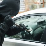 Close-up of a thief wearing balaclava breaking car window with crowbar. Car thief, car theft concept